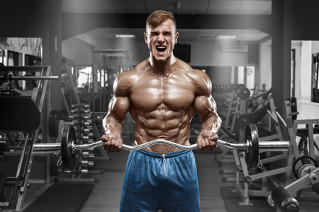 nude abs: Muscular man working out in gym doing exercises with barbell at biceps, strong male naked torso abs