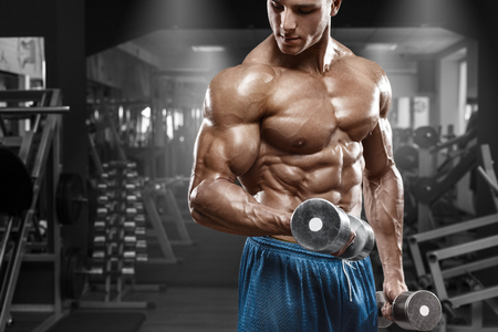 nude abs: Muscular man working out in gym doing exercises with dumbbells at biceps, strong male naked torso abs