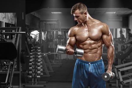 체육관에서 운동을하는 근육 질의 남자 팔뚝, 강한 남자 알몸 몸통 복근에서 아령 운동 스톡 콘텐츠