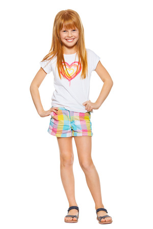 carroty: Full length a cheerful little girl with red hair in shorts and a T-shirt, isolated on the white background Stock Photo
