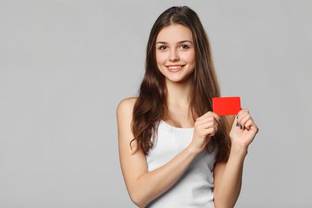 Lachende vrouw met blanco creditcard in witte t-shirt, geïsoleerd over grijze achtergrond