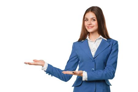 Donna sorridente che mostra il palmo della mano aperta con spazio di copia per il prodotto o il testo. La donna di affari in tuta blu, isolato su sfondo bianco Archivio Fotografico