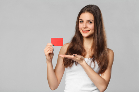 Smiling woman showing blank credit card in white t-shirt, isolated over gray background Archivio Fotografico