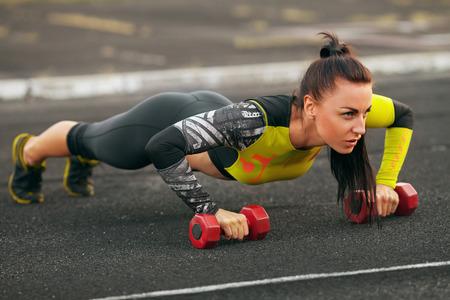 Fitness vrouw doet push-ups in het stadion, cross training workout. Sportief meisje opleiding buiten Stockfoto