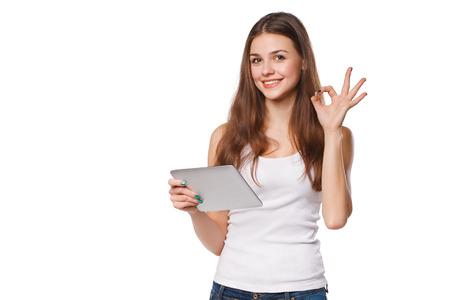 Attractive fille souriante en chemise blanche à l'aide d'une tablette montrant un signe correct. Femme avec tablette pc, isolé sur fond blanc