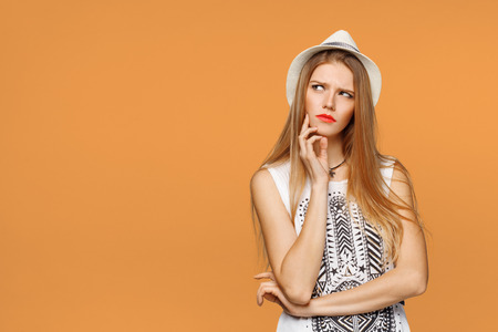 Young beautiful woman thinking looking to the side at blank copy space, isolated over orange background Stock Photo