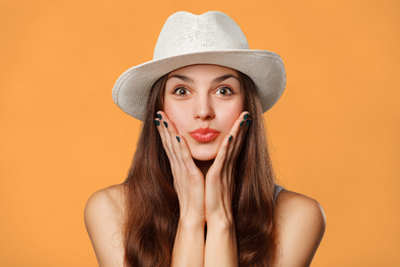 girl in a hat: Surprised happy beautiful woman looking sideways in excitement. Excited girl in hat, isolated on orange background