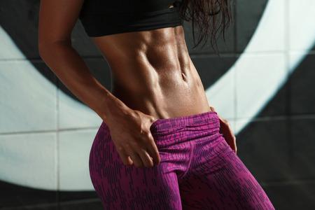 피트니스 섹시한 여자 복근과 평평한 배를 게재합니다. 아름다운 근육 소녀 모양의 복부, 슬림 허리