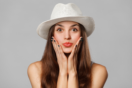 Surprised happy woman looking sideways in excitement. Excited girl in hat, isolated on gray background