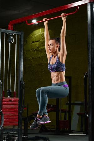 섹시한 피트 니스 소녀 행함은 체육관에서 가로 막대 위로 가져옵니다. 근육 여자 복근 모양의 복부