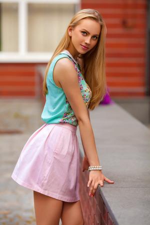 Hermosa mujer rubia con falda rosa posando al aire libre. Chica de moda