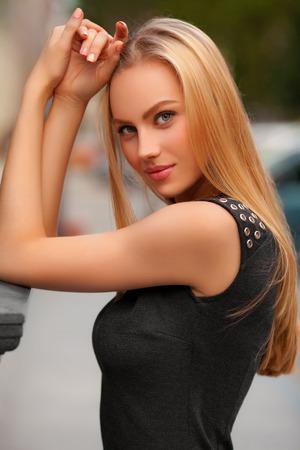 cabello rubio: Hermosa mujer sexy con vestido negro y pelo rubio posando al aire libre. Retrato de la muchacha de la manera Foto de archivo