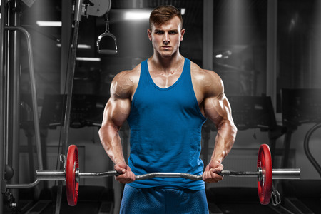 Muscular man working out in gym doing exercises with barbell at biceps, strong male Imagens