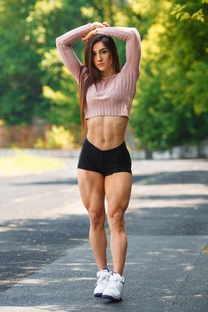 아름다운 근육 소녀 야외 포즈. 큰 쿼드 섹시한 체육 여자