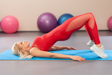 Sport woman in sportswear workout. Athletic girl doing exercise in the fitness room