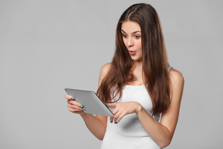 Happy girl in white shirt using tablet. Excited woman with tablet pc, isolated on grey background