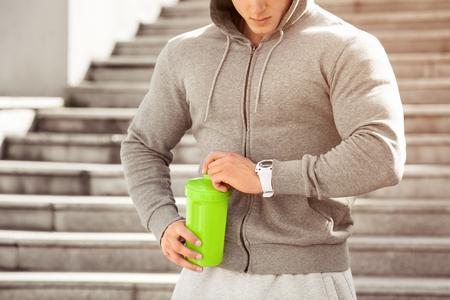De jonge actieve man gaat drinken kijkend op zijn horloge, programma, in openlucht. Knappe spier mannelijke holdingsschudbeker, drinkwater