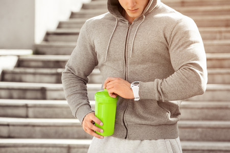 Young active man is going to drink looking at his watch, schedule, outdoors. Handsome muscular male holding shaker, drinking water