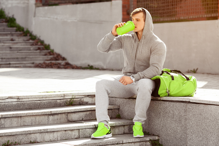 Young active man drinking water, outdoors. Handsome muscular male holding shaker Фото со стока