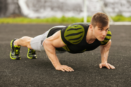 Fitness man doing push-ups in the stadium, cross training workout. Sporty male training outside