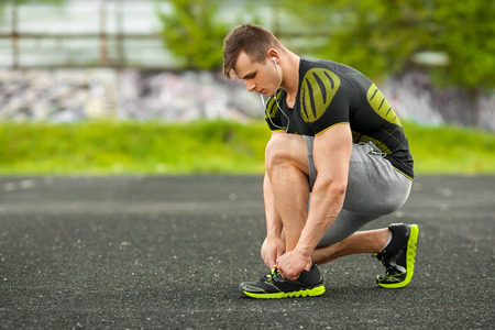 Runner man tying shoelace in the stadium, cross training workout. Sporty male training outside Stock Photo
