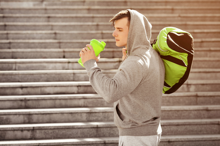 Young active man drinking water, outdoors. Handsome muscular male holding shaker Stock Photo