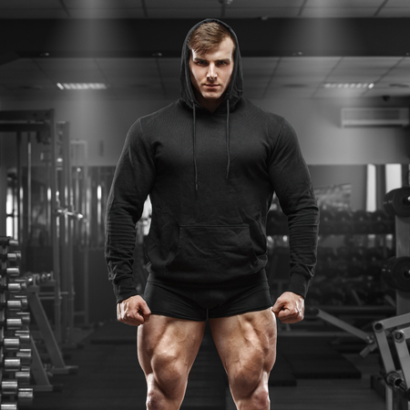 Muscular man with muscle legs in gym. Strong male in black hoodie with big quads