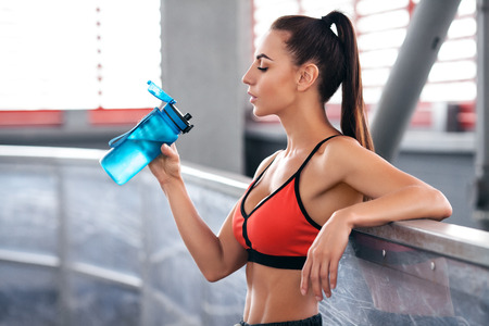 Fitness woman drinking water from a bottle. Young active girl quenches thirst