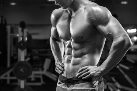 Handsome muscular man abs in gym, shaped abdominal. Strong male torso, working out Stock Photo