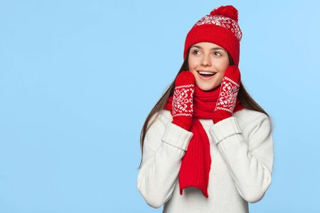 Surprised happy woman looking sideways in excitement. Christmas girl wearing knitted warm hat and scarf, isolated on blue background
