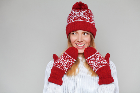 Surprised happy beautiful woman looking sideways in excitement. Christmas girl wearing knitted warm hat and mittens, isolated on gray background