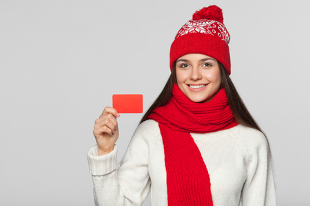 Smiling woman showing blank credit card, winter concept. Happy girl in red hat and scarf holding card, isolated over gray background Stock Photo