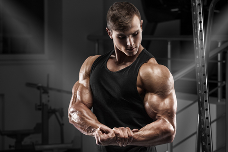 Muscular man working out in gym. Strong male showing muscles biceps Stock Photo