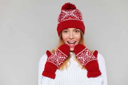 Surprised happy woman looking sideways in excitement. Christmas girl wearing knitted warm hat and mittens, isolated on gray background Stock Photo