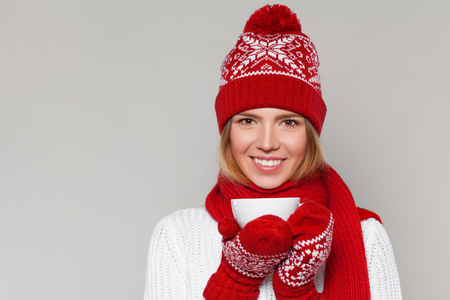 Smilling winter girl in knitted warm hat and mittens holding a cup in hands. Happy christmas woman, isolated on gray background