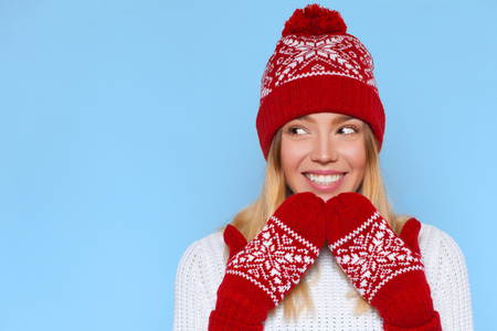 Excited woman looking sideways in excitement. Surprised christmas girl wearing knitted warm hat and mittens, isolated on blue Stock Photo