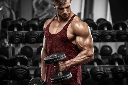 Muscular man working out in gym doing exercises with dumbbells, strong male