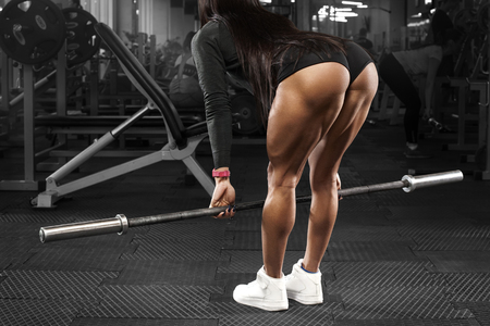 Muscular woman in gym training buttocks and legs, workout. Sexy ass in thong