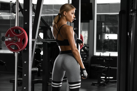 Sexy athletic girl working out in gym. Fitness woman doing exercise. Beautiful butt in legging