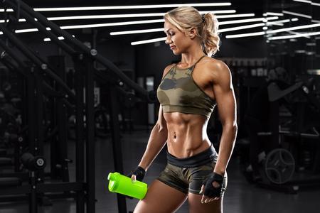 Ragazza atletica con shaker in palestra. Fitness donna con pancia piatta, addominali sagomati, addominali
