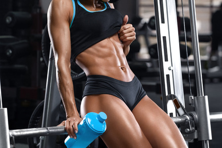 Fitness woman showing abs and flat belly. Muscular girl, shaped abdominal Imagens