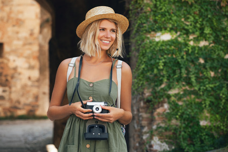 Happy traveler woman with camera. Smiling girl photographer outdoor Imagens