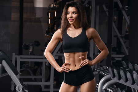 Fitness woman shaped abdominal, abs. Athletic girl with flat belly working out in gym
