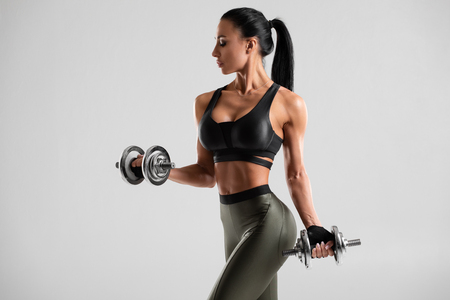 Fitness woman doing exercise for biceps on gray background. Muscular woman workout with dumbbells Imagens