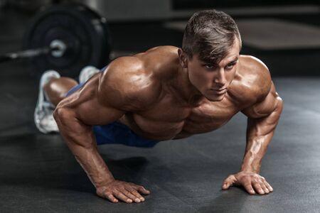 Hombre trabajando en el gimnasio haciendo ejercicios de flexiones, abdominales masculinos fuertes del torso