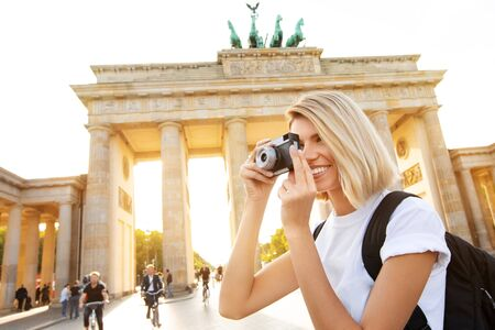Travel in Berlin, happy tourist woman with camera in front of Brandenburg Gate, Berlin, Germany Imagens