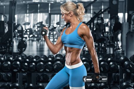 Sexy dziewczyna lekkoatletycznego poćwiczyć w siłowni. Fitness kobieta robi ćwiczenia