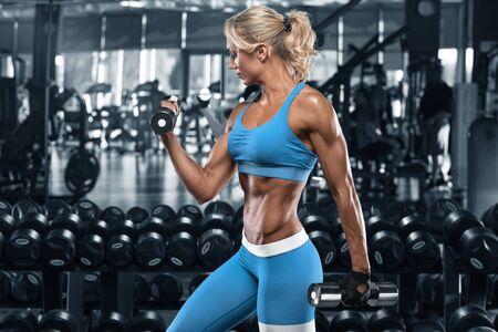Sexy sportliches Mädchen, das im Fitnessstudio trainiert. Fitnessfrau, die Übung macht