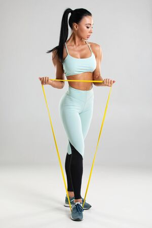 Fitness woman using a resistance band in her exercise routine. Sexy athletic girl workout with expander on gray background Archivio Fotografico