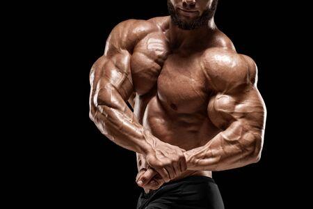 Homme musclé montrant les muscles et les biceps isolés sur le fond noir. Abdos de torse masculin de bodybuilder